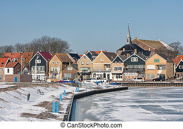 Snowy winter landscape Dutch fishing village Urk with frozen harbor