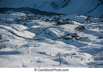 Snowy winter mountains in sun day. Georgia, from ski resort...