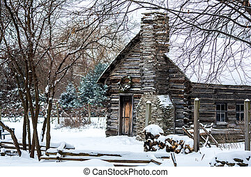 Winter Christmas scene with a log cabin covered with snow. A Christmas reef is hung on the door. Firewood is stacked in the yard.