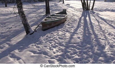 snowy wooden boat on river coast in winter