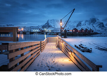 Snowy wooden pier on the sea coast with lights, houses and boats