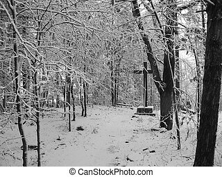 a lone cross in the woods on a snowy day