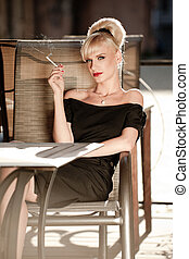 So 50s - 50s styled woman sitting in a street cafe and...