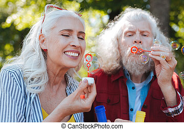 Delighted aged woman looking at the soap bubble