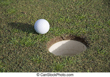 A close-up of a golf ball laying near the hole