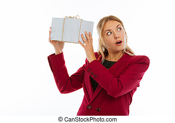 Nice young woman shaking a gift box