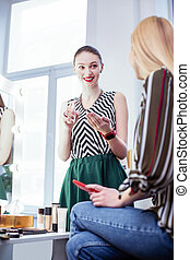 Positive cheerful woman smiling to her client