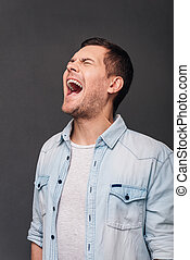 So furious! Young handsome man keeping mouth open and eyes closed while standing against grey background