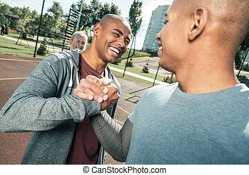 Joyful Afro American man greeting his best friend