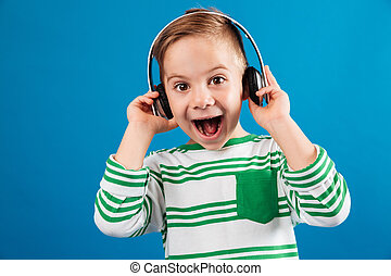 So happy young boy listening music by headphone