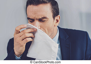 Unhappy young man sneezing