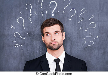 So many questions! Confused young man standing against blackboard with question marks