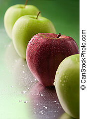 single red apple in a row on a green background