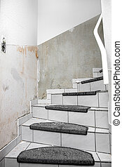 white wallpaper in a staircase is removed from the wall with a spatula