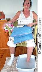 Soaking sore foot. - Mature female soaking sore foot in ...