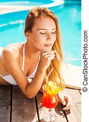 Soaking up the sun. Beautiful young woman in white bikini...