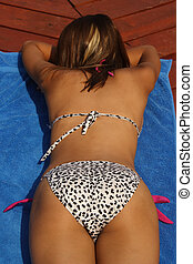 Soaking Up The Sun - Back view of a young woman sun-tanning...