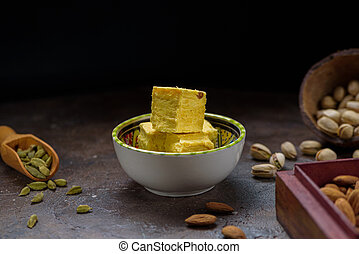Soan papdi dessert cubes in bowl, cardamom grains in wooden scoop, pistachios and almond on concrete kitchen surface with black copy space.