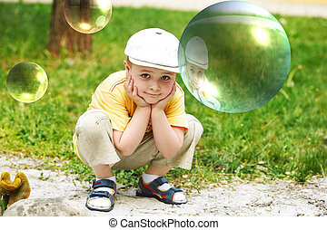 Soap bubble. The boy on a nature