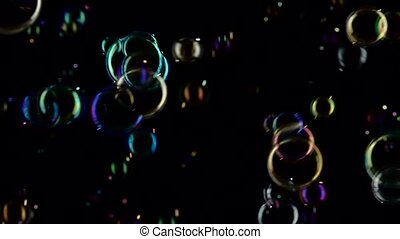Soap bubbles fly and fade in different colors. Slow motion....