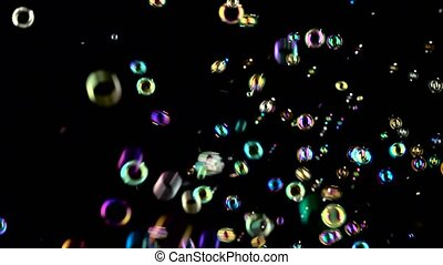 Soap bubbles start flying from the center and burst. Black...