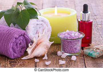 Soap, burning candle, bowl with sea salt, bottle with aromatic oil, lilac flowers and towels on wooden background.