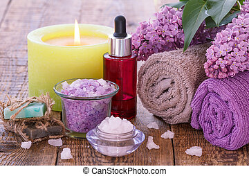 Soap, burning candle, bowls with sea salt, bottle with aromatic oil, lilac flowers and towels on wooden background.
