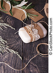 Soap making hobby. Packaging craft soap with lace and twine on wooden background