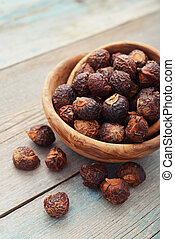 Soap nuts in bowl on wooden background closeup