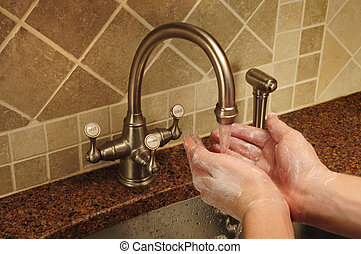 Soapy hand washing under flowing water out of a faucet -...