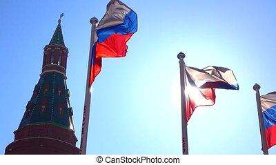 Soaring Russian flags near the Moscow Kremlin against sunny blue sky. 4K video