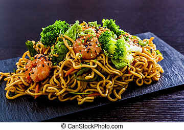 Soba noodles with shrimps and broccoli served on a slate.