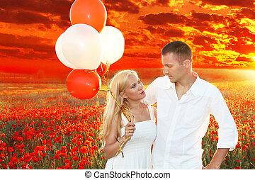 sobre, par, papoulas, campo, segurando, abraçar, feliz, balões, pôr do sol, grupo