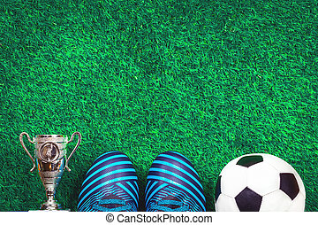Soccer ball, a cup and cleats against green artificial turf