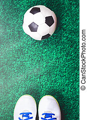Soccer ball and cleats against green artificial turf