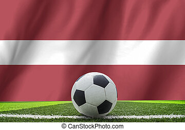 Soccer ball and national flag of Latvia lies on the green grass