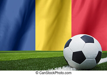 Soccer ball and national flag of Romania lies on the green grass