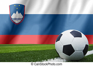 Soccer ball and national flag of Slovenia lies on the green grass