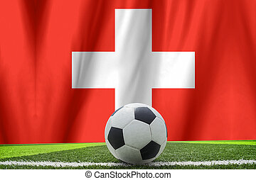 Soccer ball and national flag of Switzerland lies on the green grass