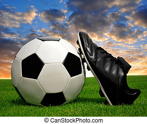 soccer ball and shoes in grass with sunset