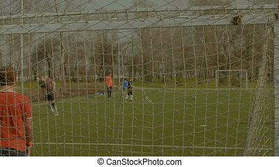 Soccer ball blazing out the crossbar after kick - Young...