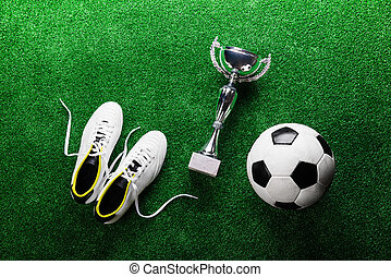 Soccer ball, cleats and trophy against green artificial turf...