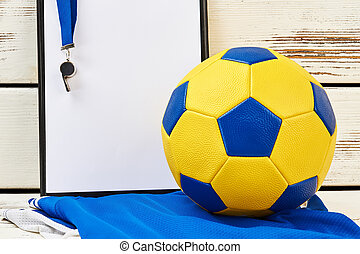 Soccer ball, clipboard, whistle, uniform