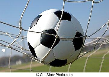 Soccer ball in net.  Scoring goal.