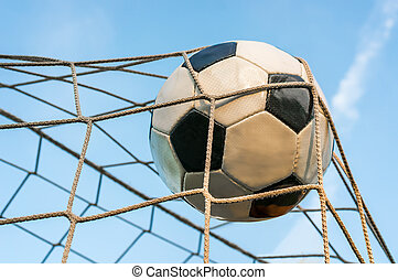 Soccer ball in the goal net with blue sky background