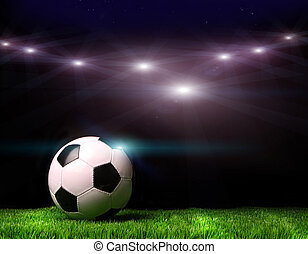 Soccer ball on grass against black background