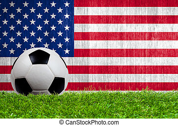 Soccer ball on grass with US flag background