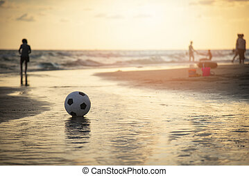 Soccer ball on sand / playing football at the beach sunset sea background
