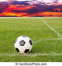 soccer ball on soccer field against sunset sky