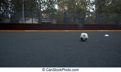 Soccer ball rolling across field. Female soccer player beats ball with her foot
